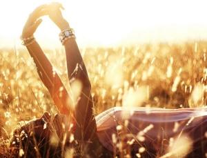 Woman-lying-in-a-field-sunlight